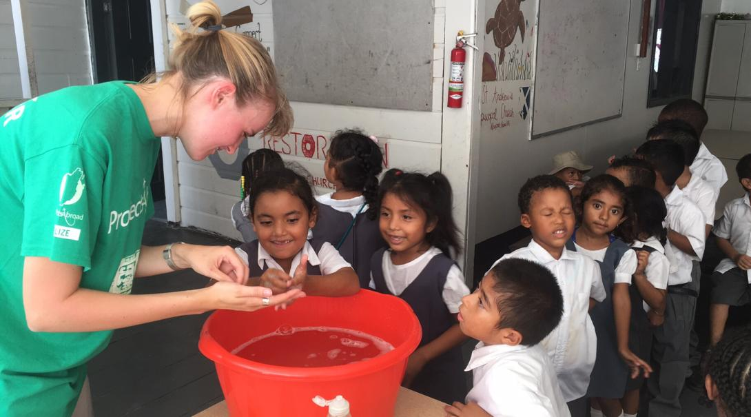 A volunteer teaches her students the most effective way to wash their hands in Belize